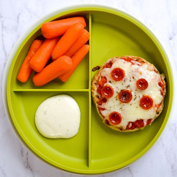 a green sectioned kid's plate on a marble counter top with a pepperoni english muffin pizza, carrots, and ranch dip