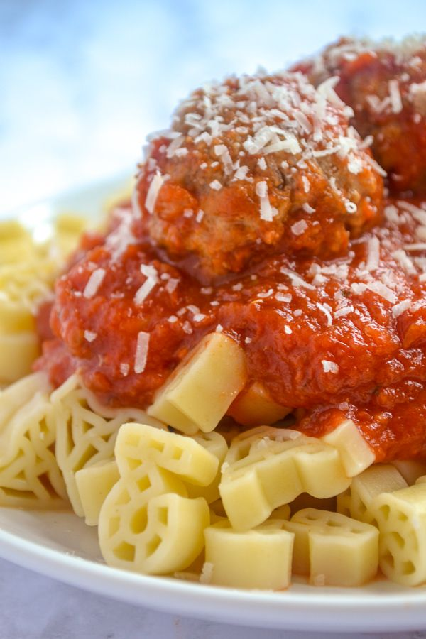 a picky eater recipe of big meatball covered in cheese and tomato sauce on top of ABC pasta