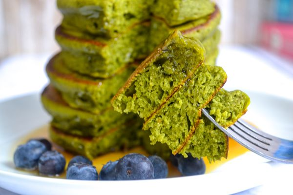 a fork holding a layer of sliced green spinach pancakes with a stack in the back ground on a white plate with blueberries and syrup.