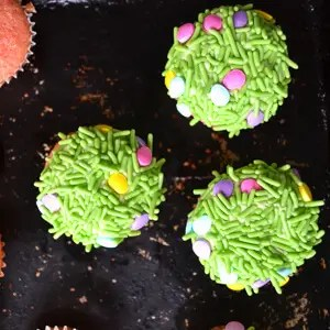 cupcakes topped with bright green sprinkles and pastel egg candies to look like grass
