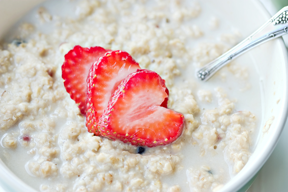a bowl of oatmeal topped with heart shaped strawberries