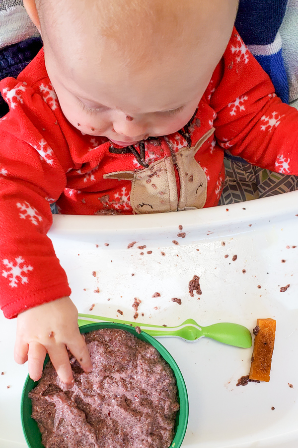 a baby in red pajamas at a high chair putting her hand in a bowl of baby chiap pudding