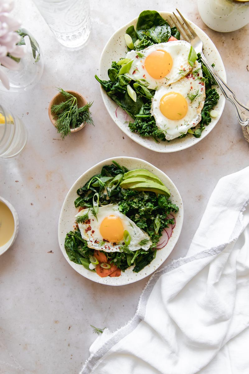 These hearty Paleo Breakfast Bowls are filled with sauteed greens and eggs and topped with a rich, nutty Tahini Sauce--the perfect nutrient-packed way to start the day!