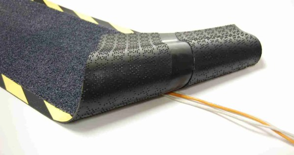 Morland cable Protect Mat turned back, covering a single yellow cable on a white background