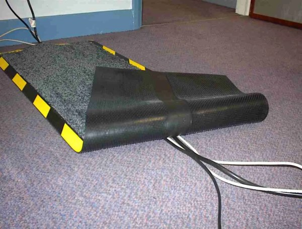 Photograph of a Morland cable protect mat in use in an office turned back showing how it covers several cables