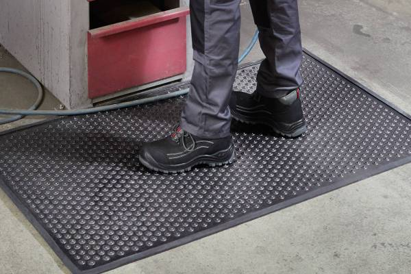 Close up of feet in boots standing on a Morland Active Industrial Rubber Anti-Fatigue Mat