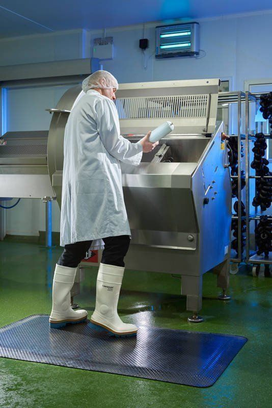 Person in white coat and white rubber boots in a food preparation area standing on a Morland Comfort Industrial Rubber Mat