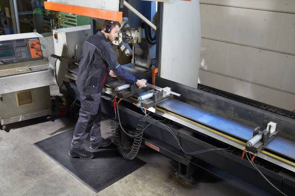 Person standing at an industrial workstation on a Morland Comfort Structure Industrial Rubber Anti-fatigue mat