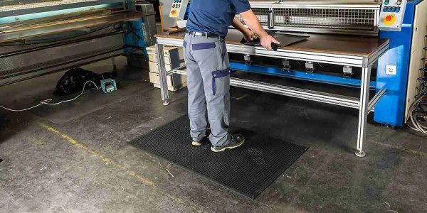 man at an industrial workstation standing a Morland Comfort Structure Anti-fatigue mat