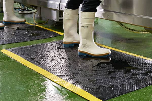 A worker with white dunlop boots standing on Morland Comfort Safety Anti fatigue mat with water around
