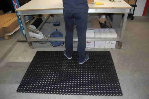 A person stood on single Morland Robust Industrial Rubber Doormat with full drainage holes at a packaging table