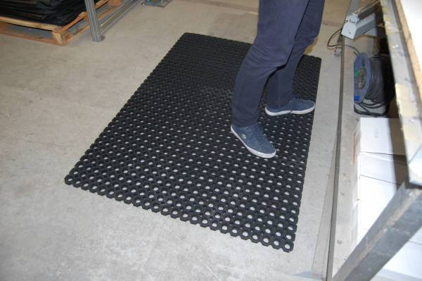 A person stood on single Morland Robust Industrial Rubber Doormat with full drainage holes at a table in a workshop