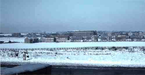 A group of houses behind a field covered with snow