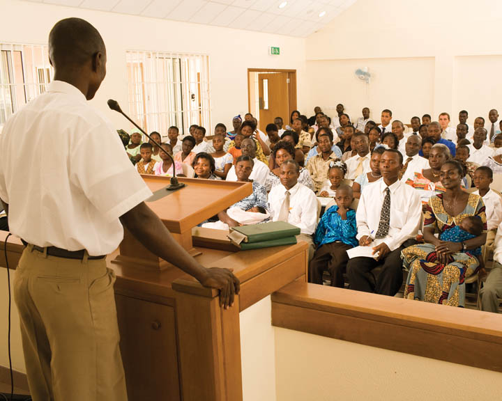 A photo of an African-American man giving a talk to a predominately African-American congregation at a Mormon church service.