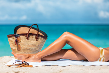 beach vacation woman legs lying on the sand after laser hair removal
