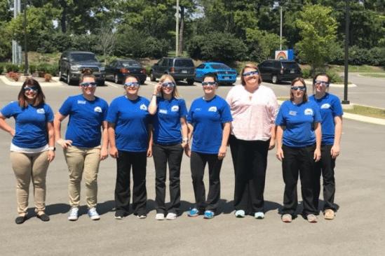 eight women outside in matching blue shirts