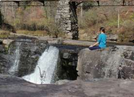 Woman performing yoga outside by a waterfall