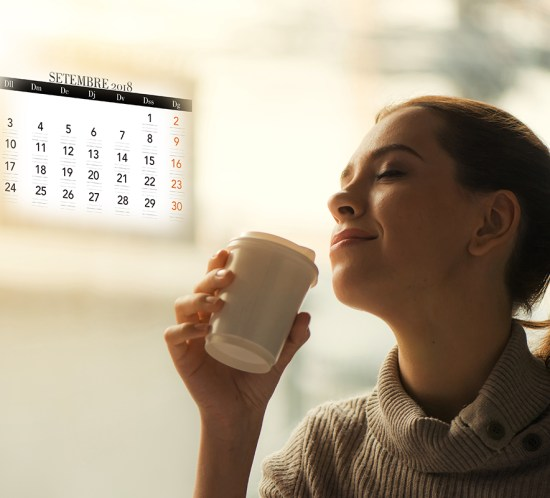 Woman drinking coffee at home with sunrise streaming in through