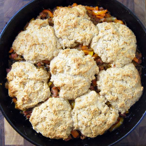 Buttermilk drop biscuits top a peppers, sausage, and onion skillet