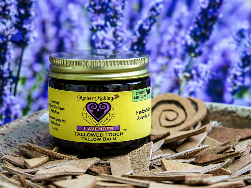 2oz jar of Lavender Tallowed Touch Tallow Balm in a shallow plate with cut leather and lavender flowers background.
