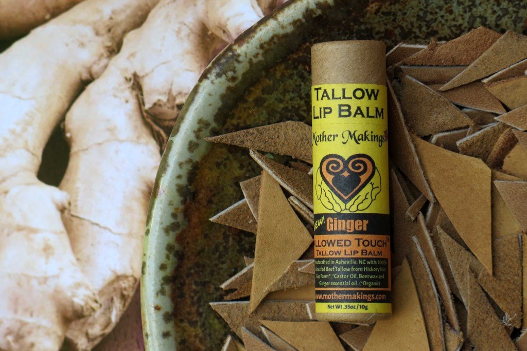 Ginger tallow lip balm in a paper tube laying in a dish of cut tan leather and a photo of ginger underneath.