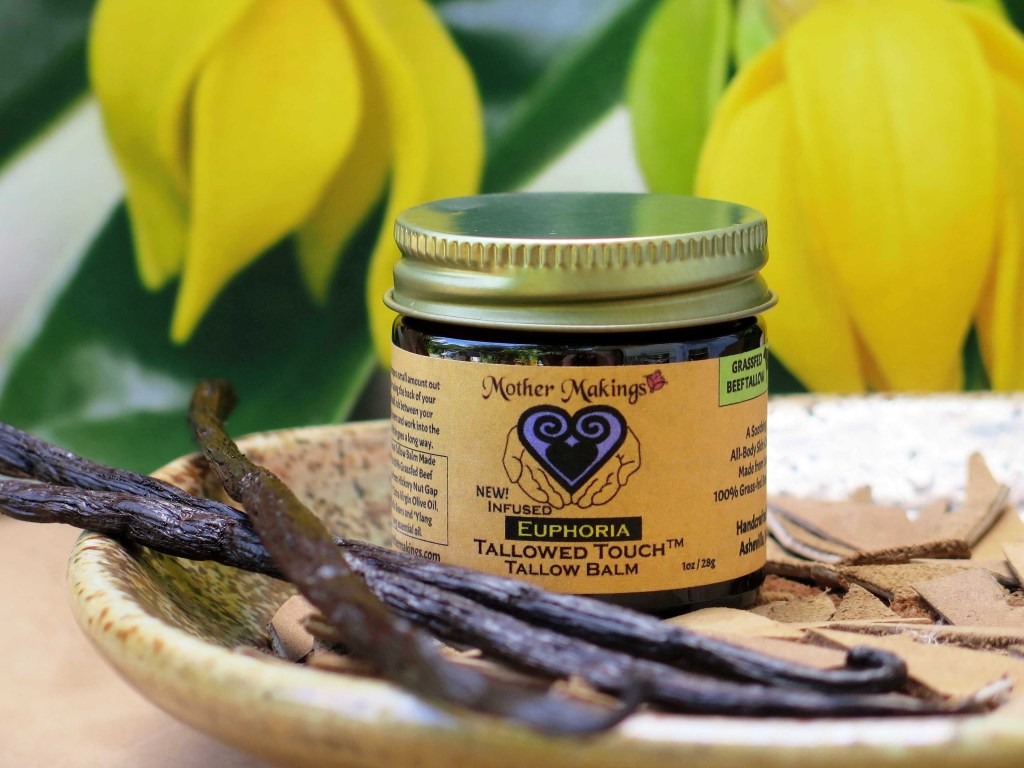 Infused Euphoria Tallow Balm jar with black vanilla beans and bright yellow ylang ylang flowers in the background.