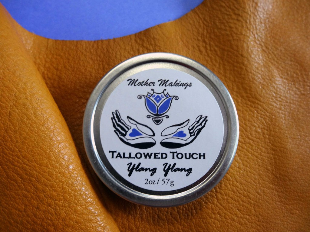 Silver tin on an ochre yellow piece of leather with cornflower blue background. Label says: Mother Makings Tallowed Touch Ylang Ylang and weightwith old logo of two cupped hands and a purple blue flower floating above them.