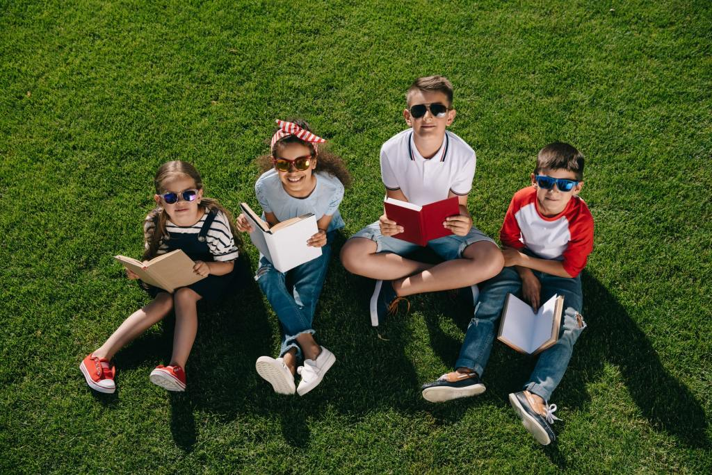 High angle view of cute multiethnic kids in sunglasses reading books while sitting on grass and