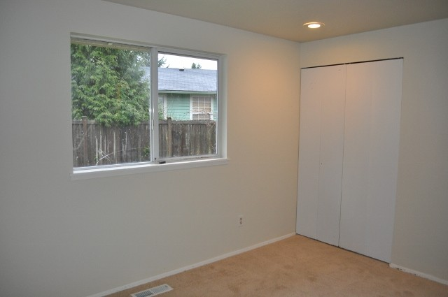 before house tour empty white bedroom white walls folding closet doors small sliding window