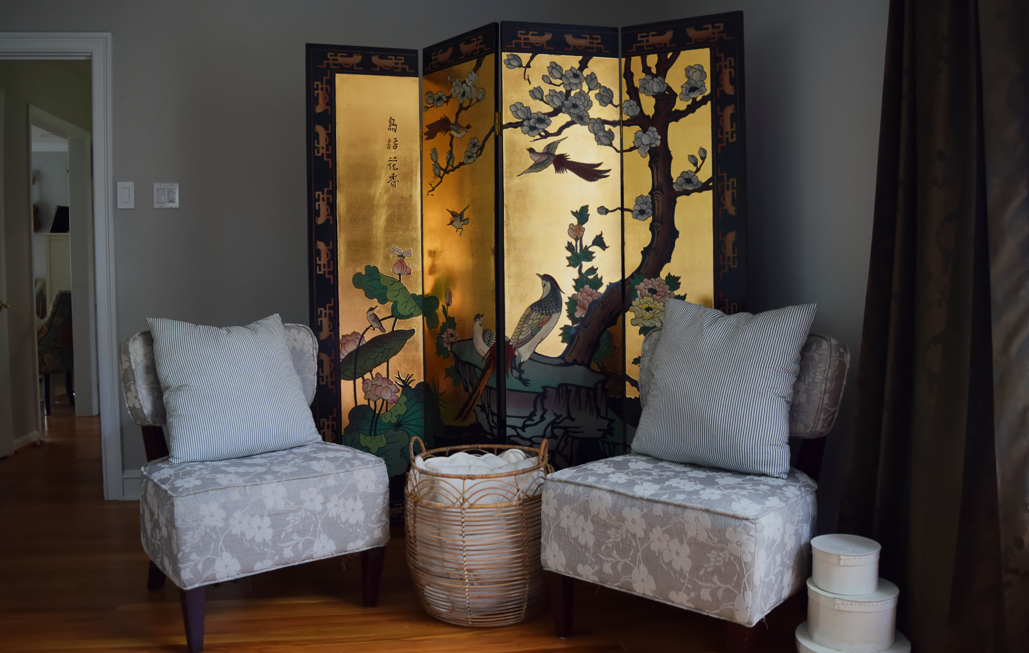floral chairs and basket in front of gold chinoiserie coromandel floor screen hiding our elliptical