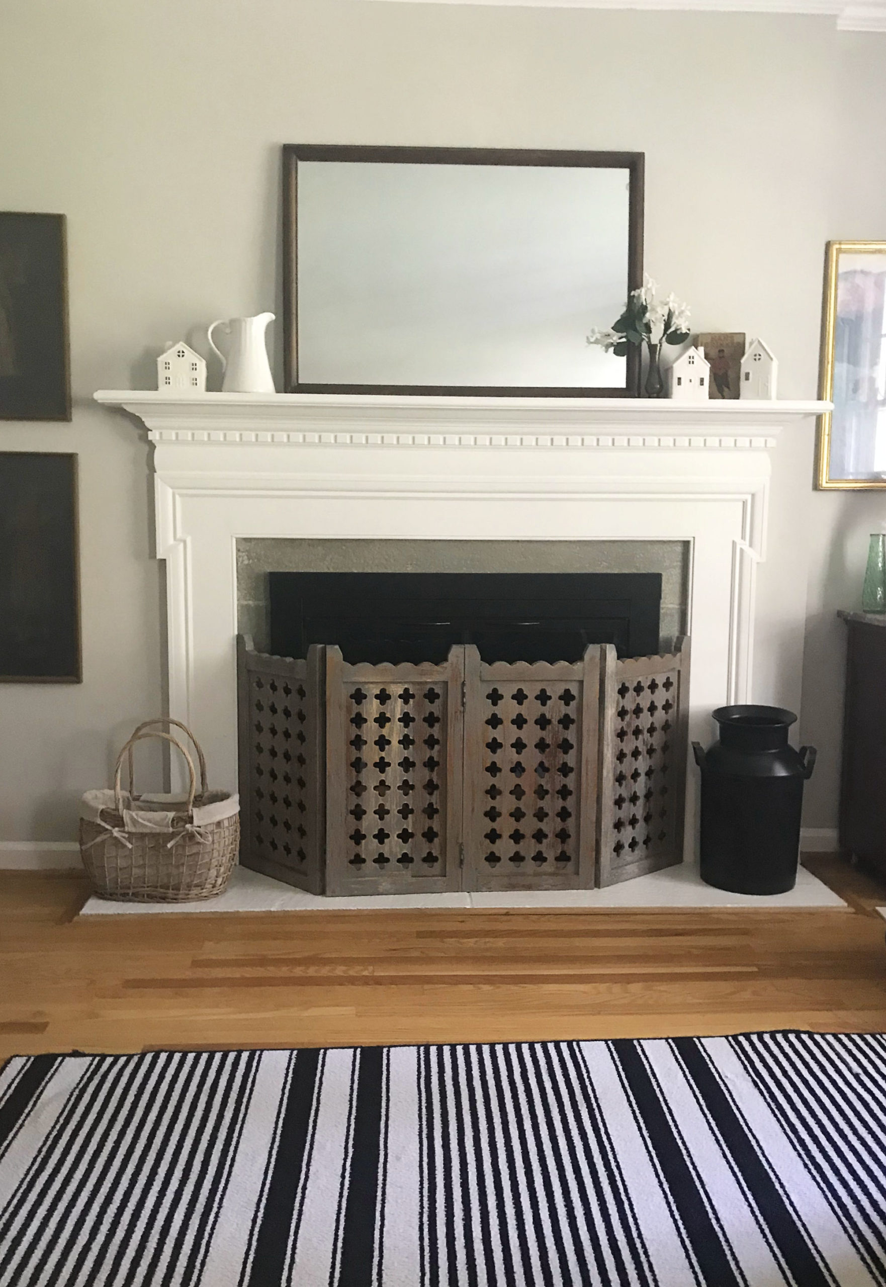 black and white striped rug in front of white wood fireplace mantel