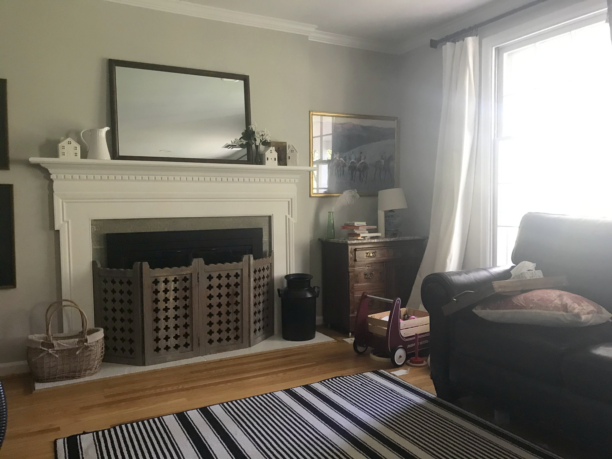 living room before black white striped rug in living room with mirror and ceramic houses on fireplace mantel
