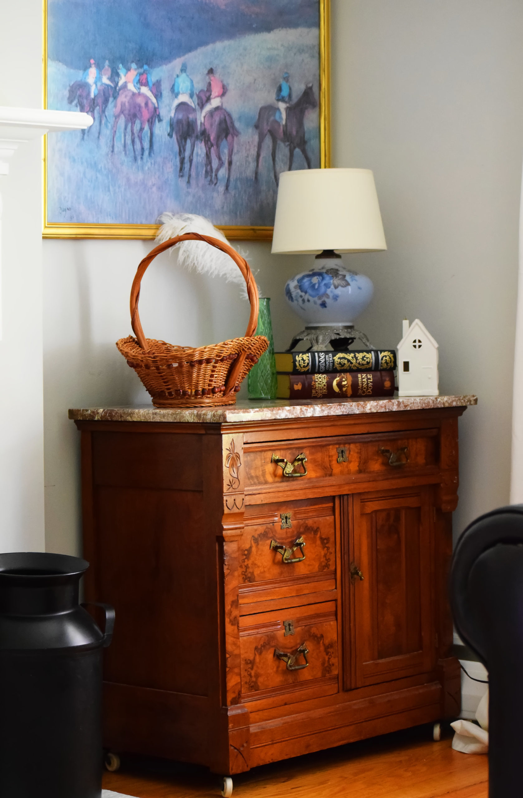 burlwood cabinet with basket blue lamp and horse painting