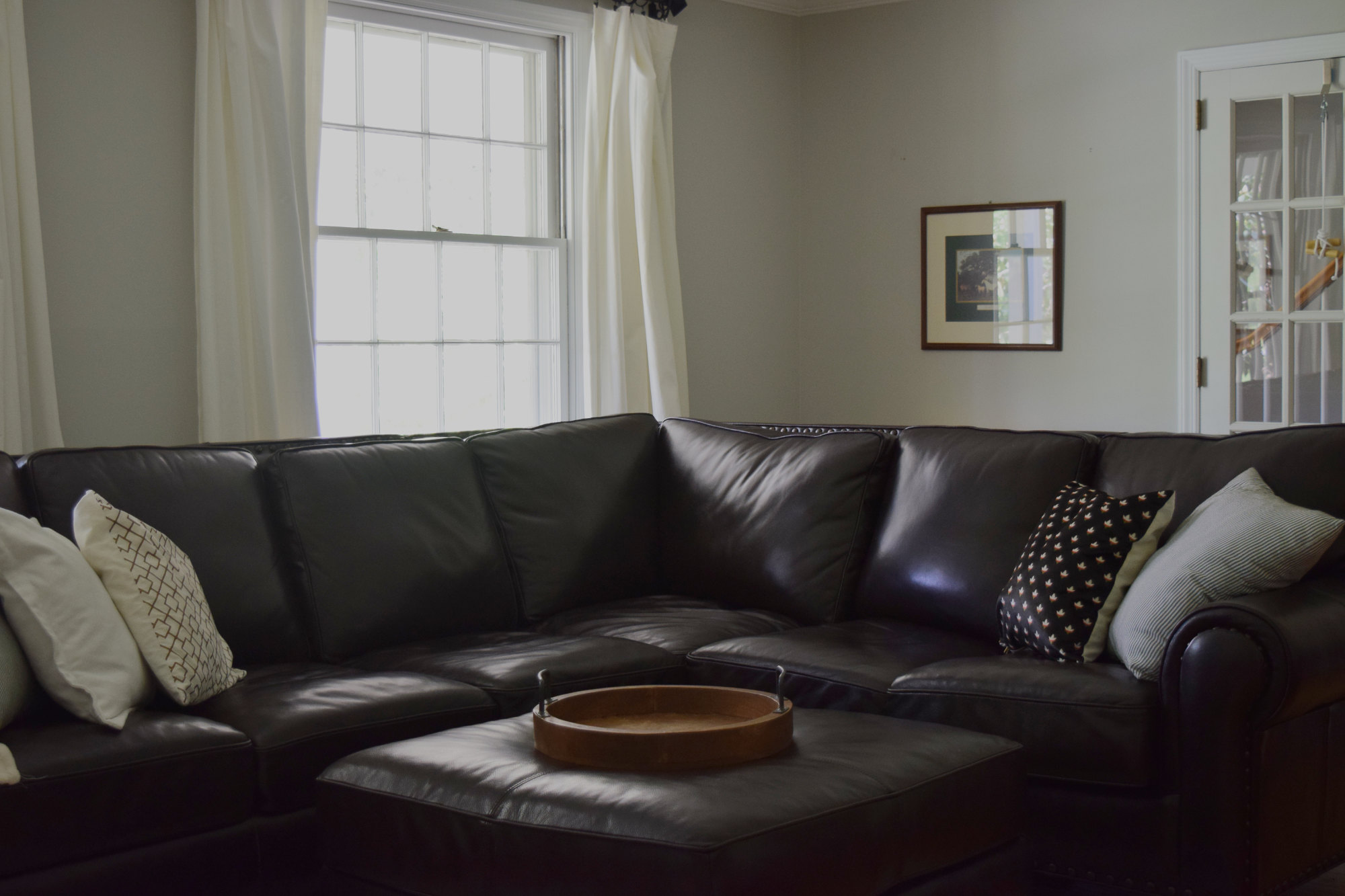 dark brown leather sectional with tray and white curtains motif motif pillow in living room