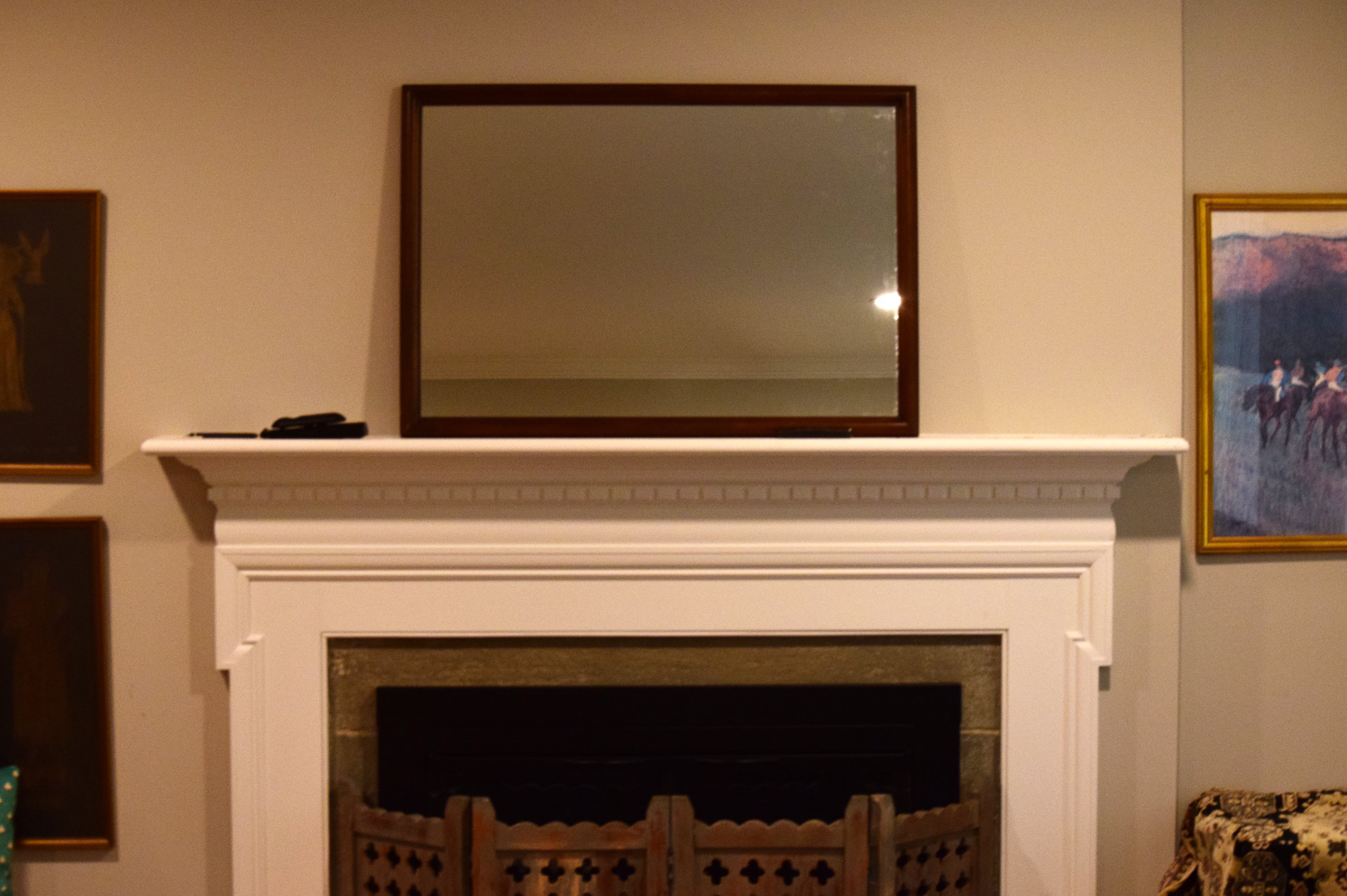 dark framed mirror on fireplace mantel with tv remotes