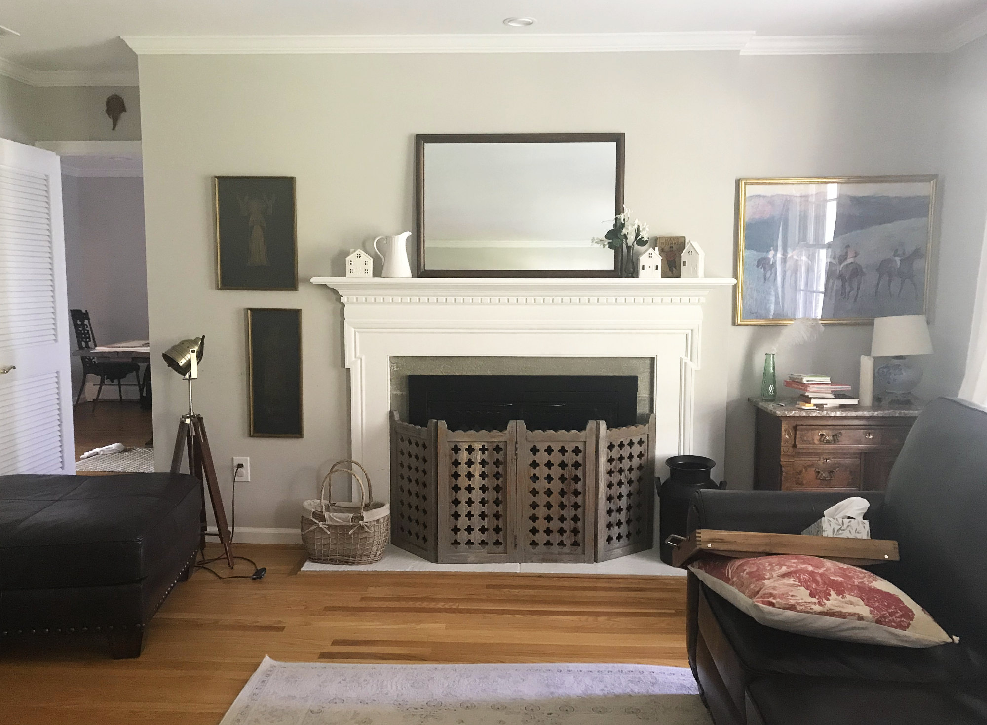 white fireplace mantel in living room with quatrefoil screen and lighter rug