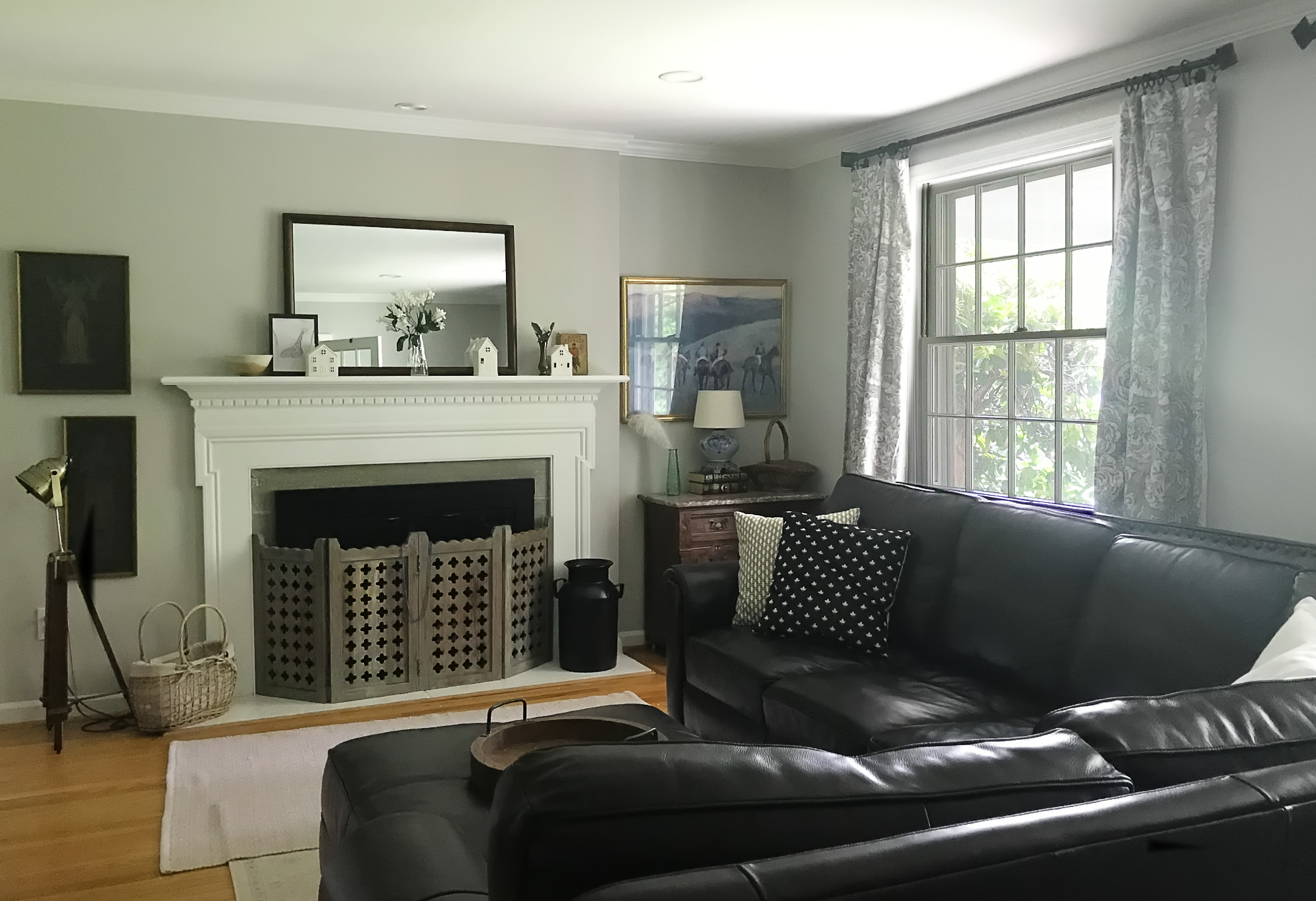 gray living room with white fireplace and dark leather sectional