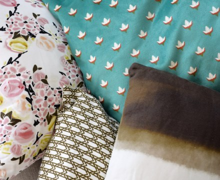 green turquoise and floral pillows in a pile