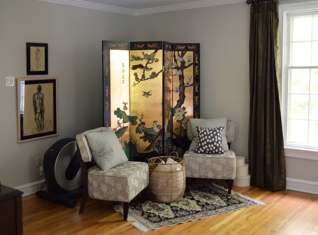 floral chairs and chinese screen hiding elliptical in bedroom
