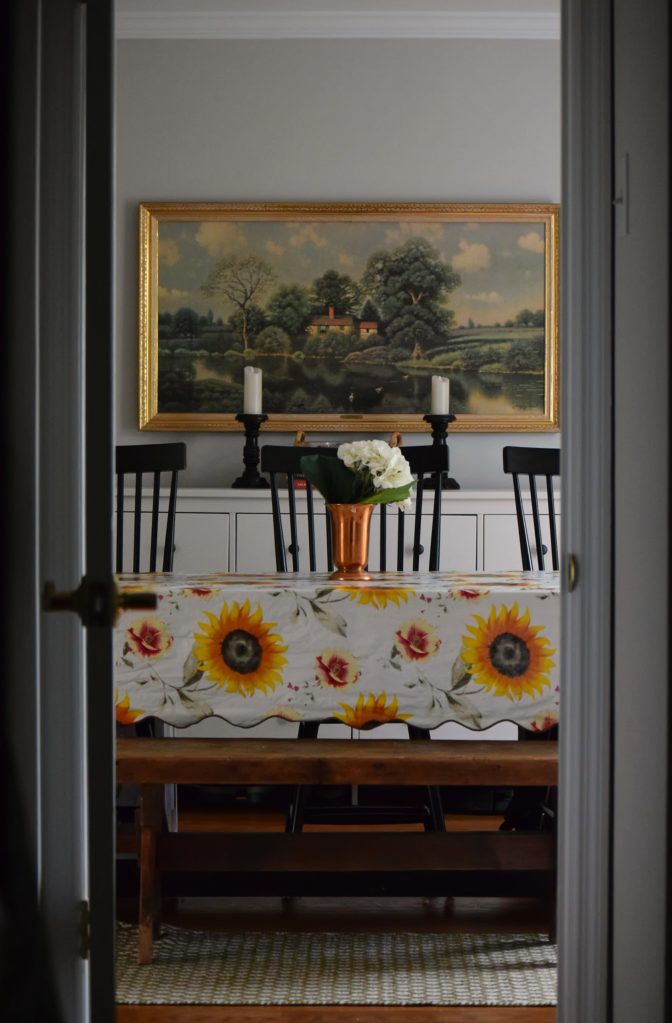 sunflower vinyl tablecloth in dining room with black shaker chairs