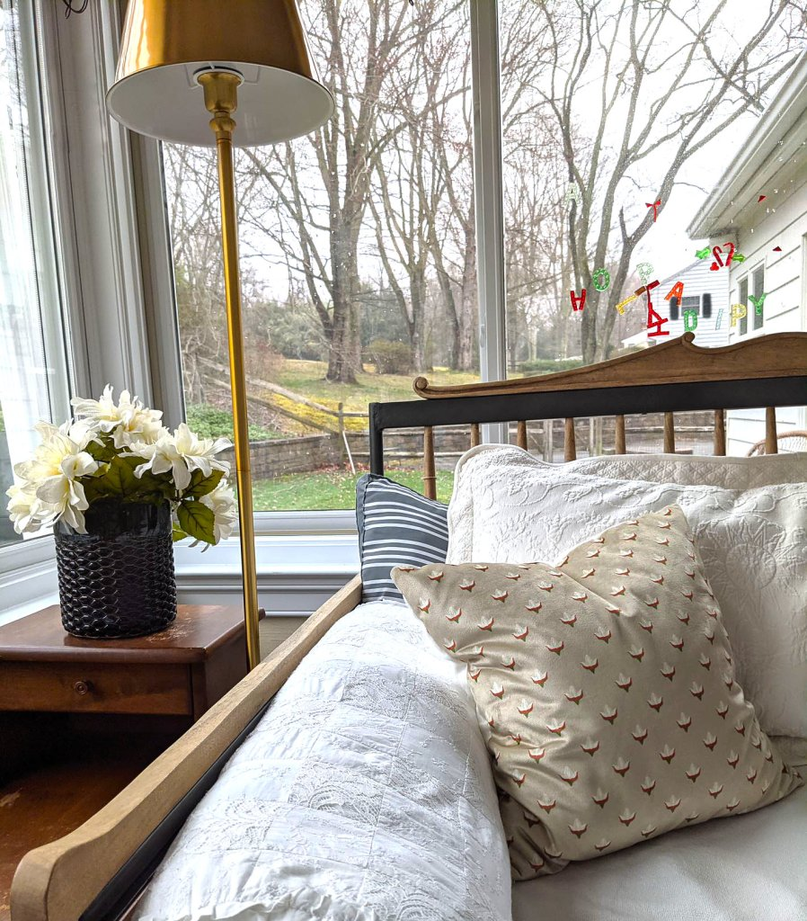daybed brass lamp and flowers by windows