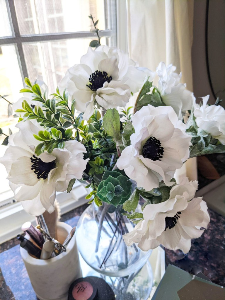 clean artificial flowers and greenery mixed together in a countertop anemone arrangement