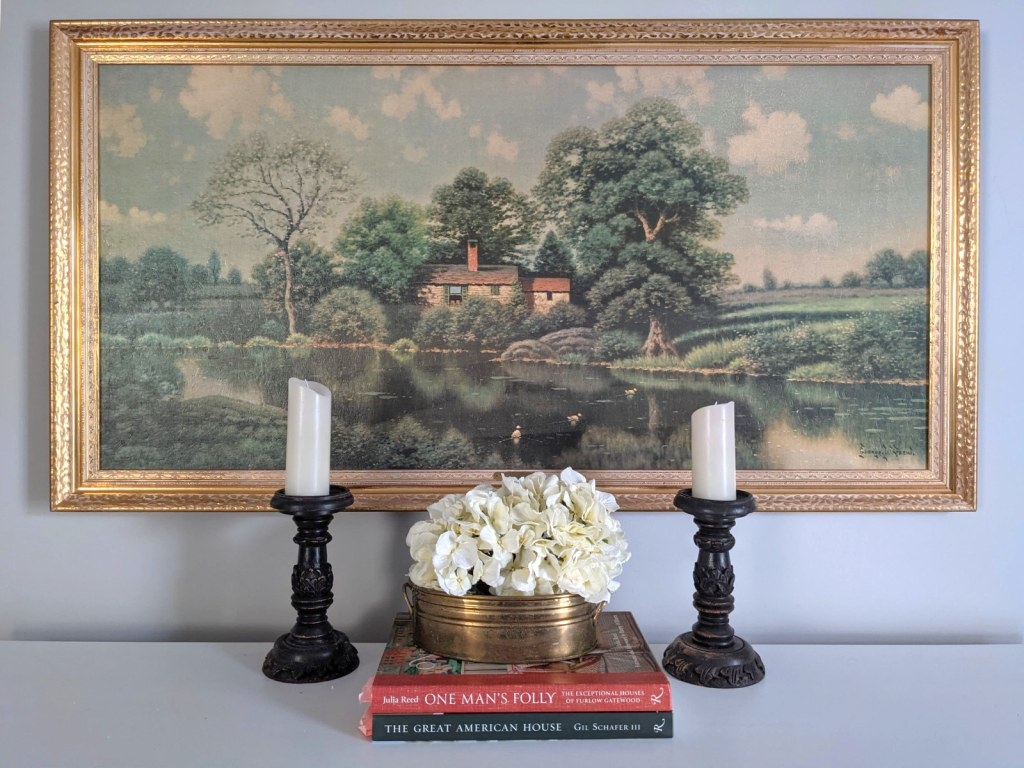 silk hydrangeas pillar candles books in front of landscape painting