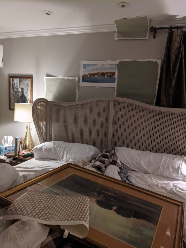 farrow and ball paint swatches and art on bed