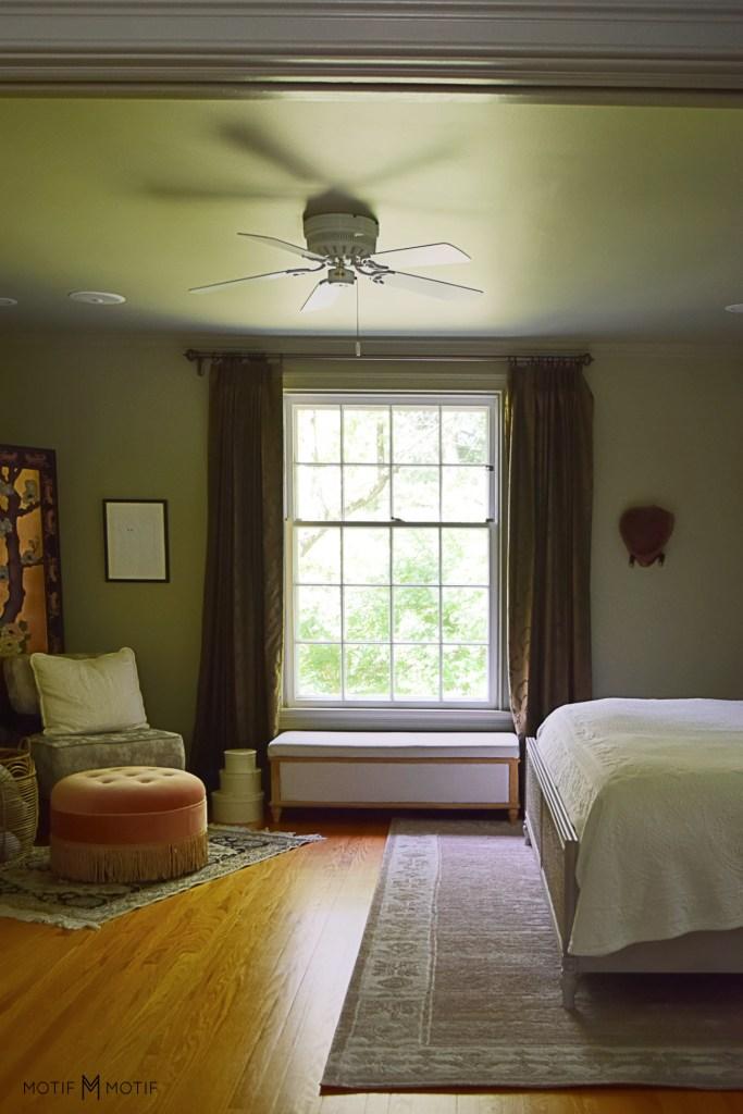 window bench in green bedroom with white ceiling fan