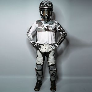 Front view of model wearing white and grey motocross jersey, gloves and pants with hands on hips
