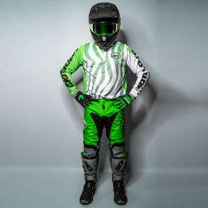 Front view of model wearing and white motocross jersey, pants, gloves and helmet, with hands on hips