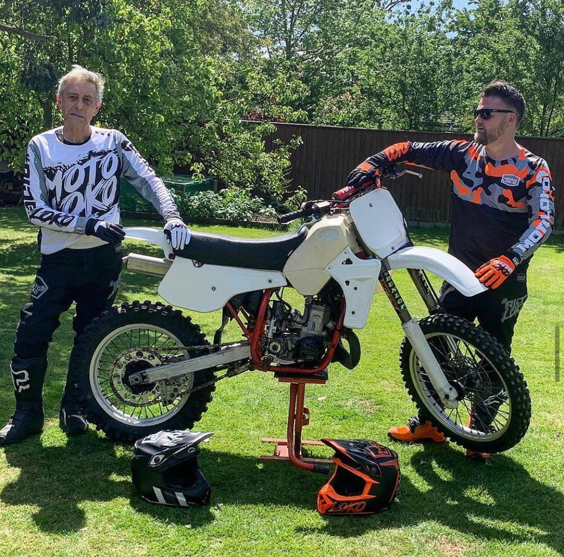 Father and son wearing motocross kits, standing either side of bike