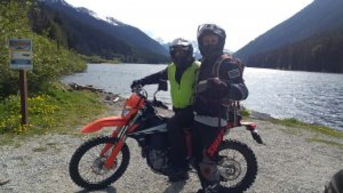 A KTM motorcycle stopping for a break by the Duffey Lake on a motorcycle tour