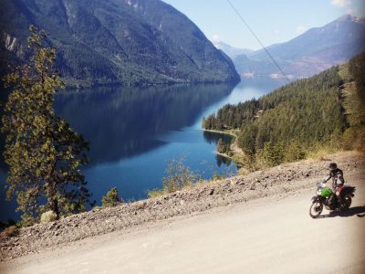 Single motorcycle on tour riding high above Anderson lake on the highline